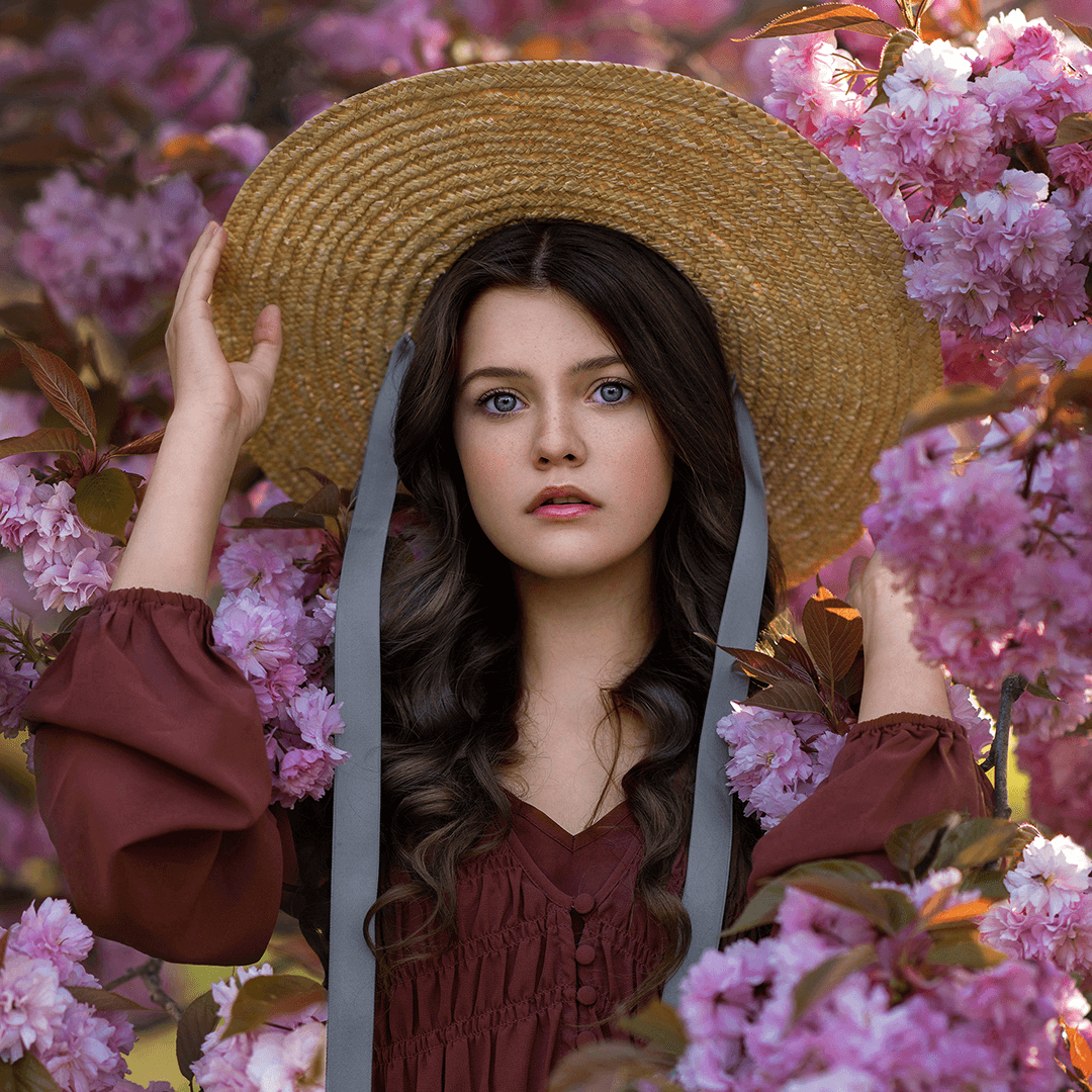 girl with straw hat surrounded by cherry blossom